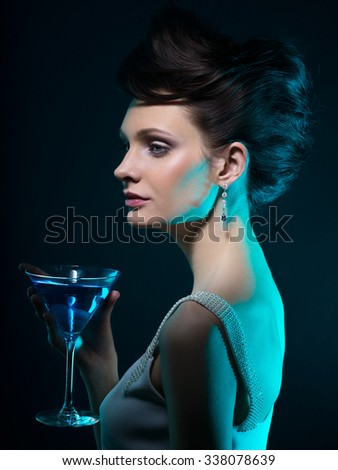 Young woman with martini glass in blue light on dark background  - stock photo