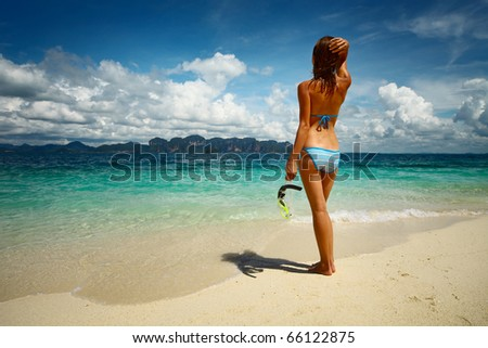 young woman with mask standing on sand and going to snorkel - stock photo