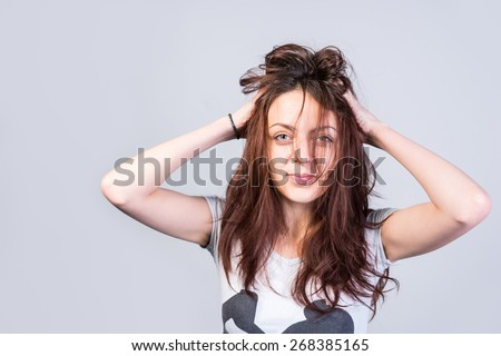 Young woman with messy tousled hair holding her hands to her head with a wry expression at her disheveled appearance, isolated on grey - stock photo