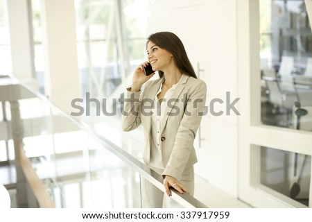 Young woman with mobile phone in the office - stock photo