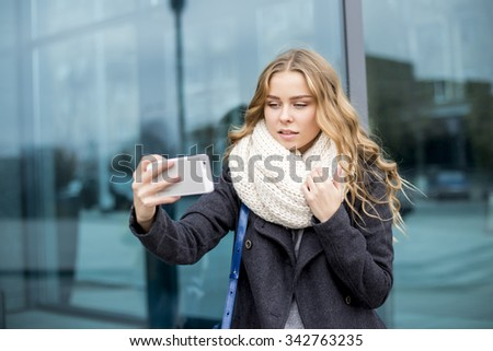Young woman with mobile phone on the street - stock photo