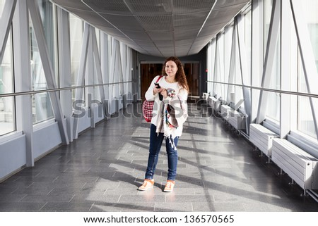 Young woman with mobile phone standing in airport hall - stock photo