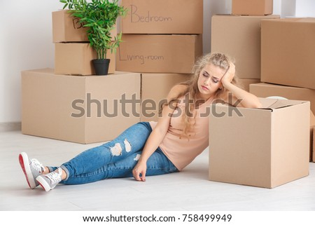 Young woman with moving boxes on floor in room