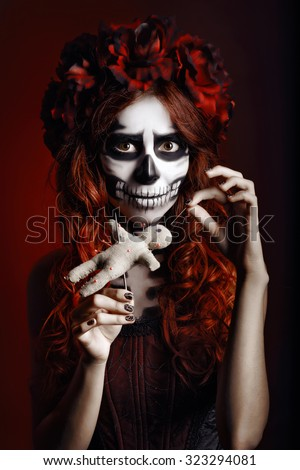 Young woman with muertos makeup (sugar skull) piercing a voodoo doll - stock photo
