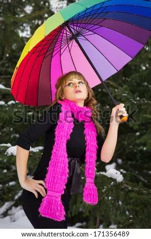 Young woman with multicolor umbrella at winter forest