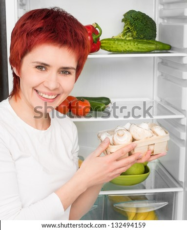 young woman with mushroom against the refrigerator with food