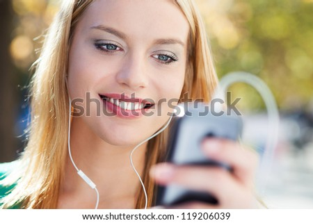 Young woman with music player - stock photo