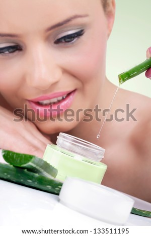 Young woman with natural aloe vera cream ready for beauty treatment