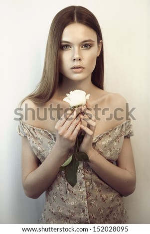 Young woman with natural make-up, pretty long hair and white rose in her hands looking at camera - stock photo