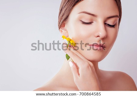 Young woman with natural makeup holding a flower. Organic cosmetics concept