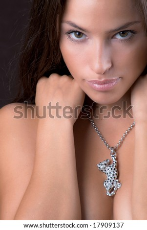 young woman with necklace, studio shot dark background - stock photo