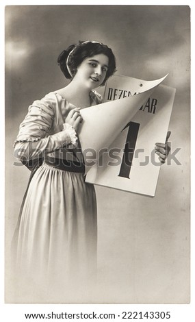young woman with New Years calendar. antique picture with original scratches and film grain - stock photo