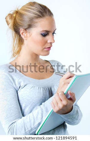 young woman with notebook and pen planning her daily schedule