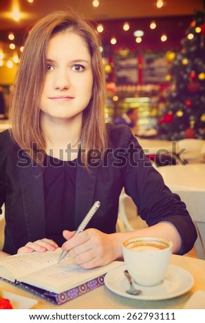young woman with notebook in modern cafe - stock photo