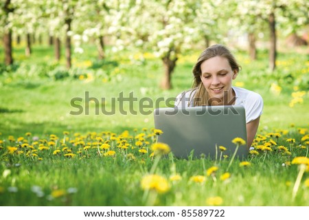 Young woman with notebook in park looking at notebook computer