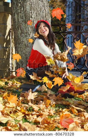 young woman with notebook sits under tree, on fall leafs background