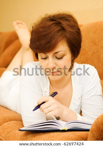 Young woman with notepad or organizer writing at bedroom