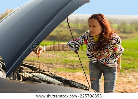 young woman with oil probe bent over car engine - stock photo