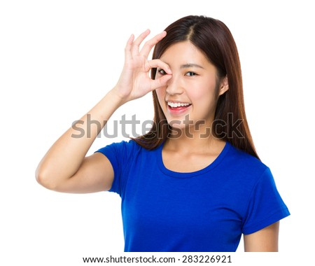 Young woman with ok sign on her eye - stock photo