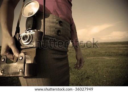 Young woman with old camera outdoor. Retro style. - stock photo