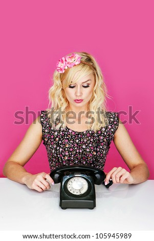Young woman with old dial up telephone. - stock photo