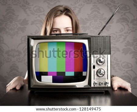 young woman with old retro tv - stock photo