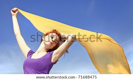Young woman with open arms keep yellow silk on wind. - stock photo