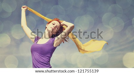 Young woman with open arms keep yellow silk on wind. Photo with bokeh at background. - stock photo