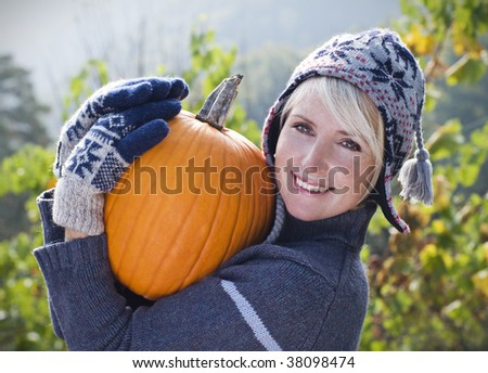 Young woman with orange pumpkin close up shoot - stock photo