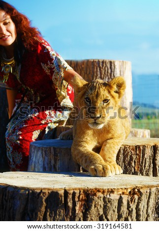young woman with ornamental dress and gold jewel playing with lion cub in nature - stock photo
