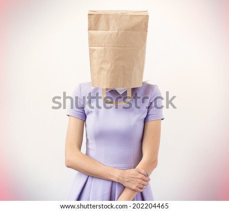 Young woman with paper bag over her head - stock photo