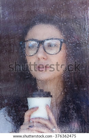 Young woman with paper cup of coffee or tea looking through window in a rainy day.  Business woman with paper cup of coffee looking through blurred window in rainy day. Morning coffee and water drops. - stock photo