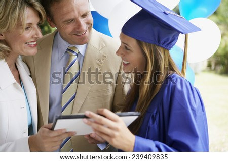 Young Woman With Parents at Graduation - stock photo