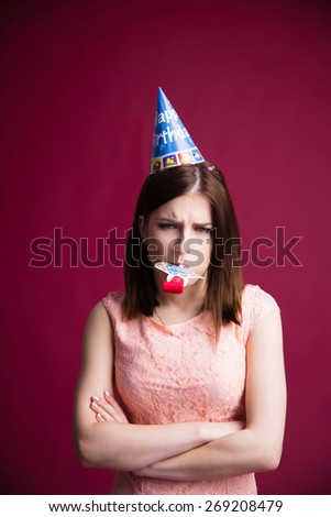 Young woman with party whistle and arms folded over pink background. Looking at camera - stock photo
