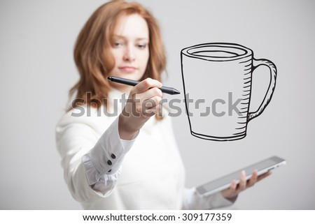 young woman with pen draws a Cup of coffee on grey background - stock photo