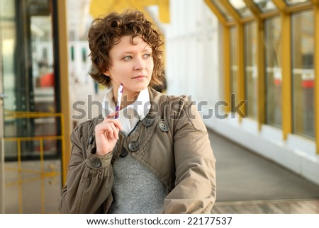 Young woman with pen thinking - stock photo