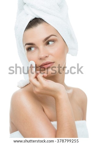 Young woman with perfect complexion cleaning her face skin