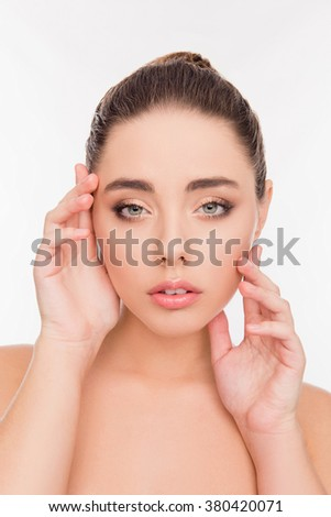 Young woman with perfect skin holding hands near face, close up photo - stock photo
