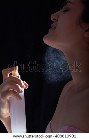 young woman with perfume in hand isolated on black - stock photo