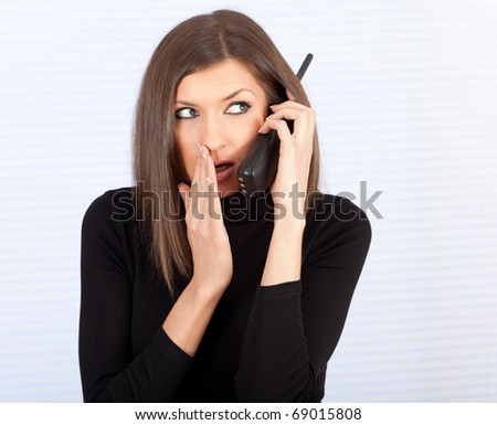 young woman with phone - gossips in secret - stock photo