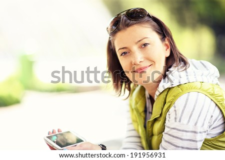 Young woman with phone sitting in the park - stock photo