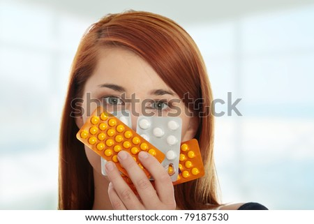 Young woman with pills - focus on pills - stock photo