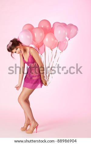 Young woman with pink balloons on pink background. - stock photo