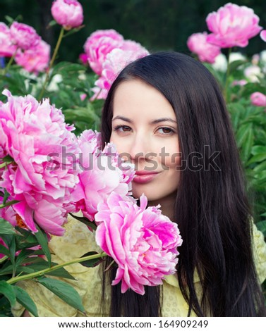 Young woman with pink peonies