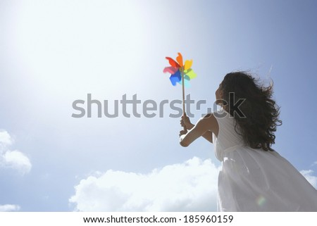 Young woman with pinwheel against sky (low angle view) - stock photo