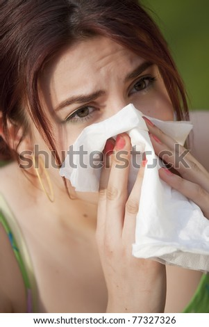 young woman with pollen allergy sneezing in handkerchief - stock photo