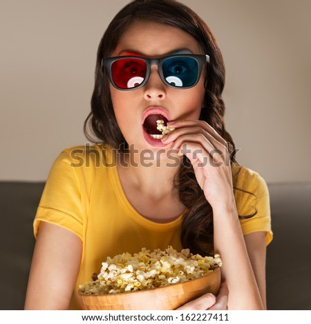Young woman with popcorn and 3d glasses watching movie at home