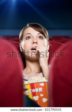 Young woman with popcorn at the cinema - stock photo