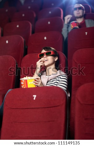 Young woman with popcorn in 3D movie - stock photo