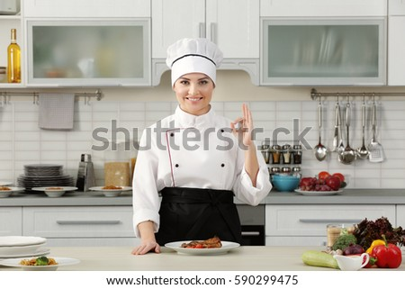 Young woman with prepared meat dish in modern kitchen